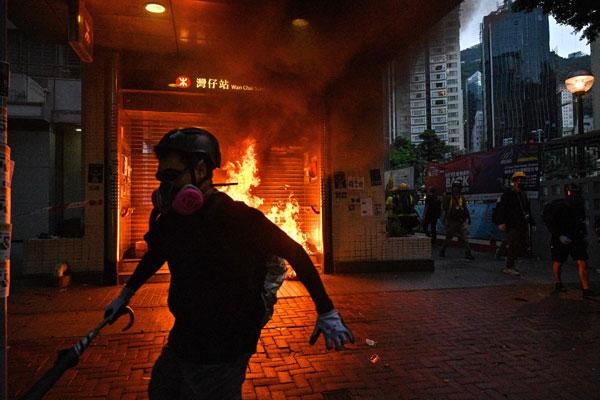 湾仔港铁站出口遭示威者纵火燃烧。(法新社)