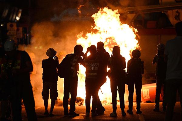 湾仔街上被人纵火,媒体记者在录影拍照。(法新社)