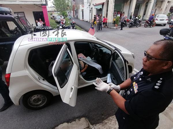 阿都查基(右)与警员准备从死者所驾驶的车内,取出遗体。