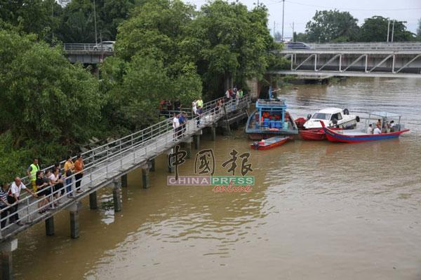 失踪者的家属站在情人桥上,注意着搜救队伍的搜寻工作。
