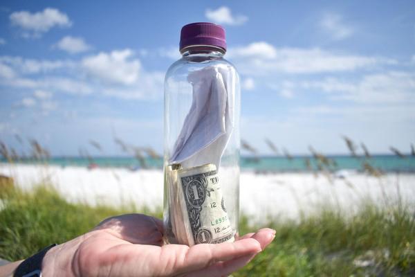 玻璃瓶中装有穆林斯骨灰、美钞和纸条。