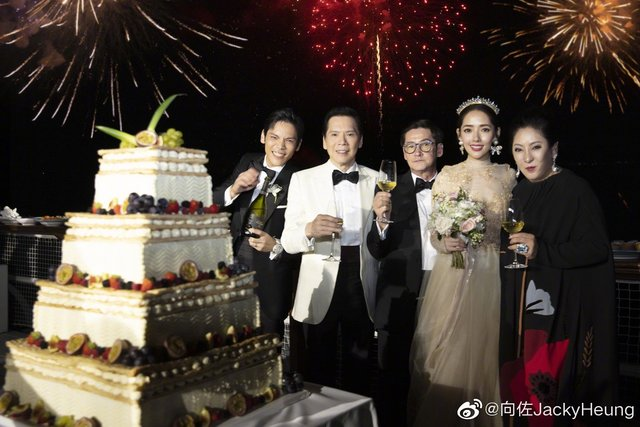 一家人在结婚蛋糕旁合照。图/向佐微博