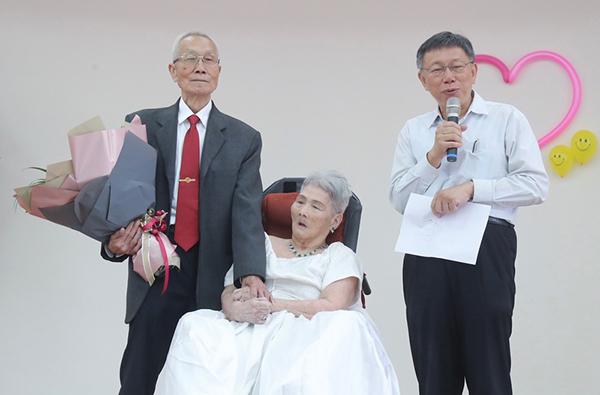 83岁的阿公詹瑞东(左)与太太韩水金(中)圆梦,在内湖五分区民活动中心举办婚礼,台北市长柯文哲(右)出席祝福。