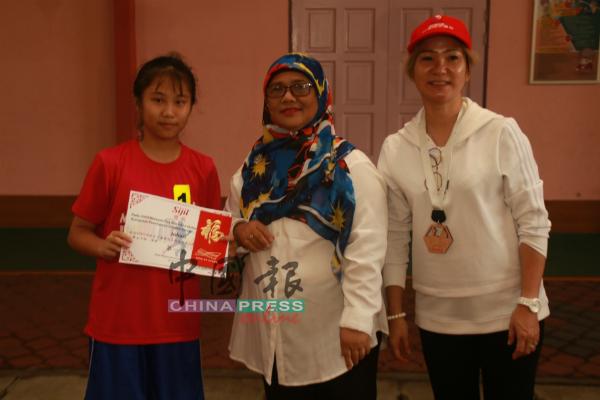 波德申社会发展局的代表诺莱妮(中)颁发奖状和奖牌给小学女子组优胜奖,右为陈凤兰。