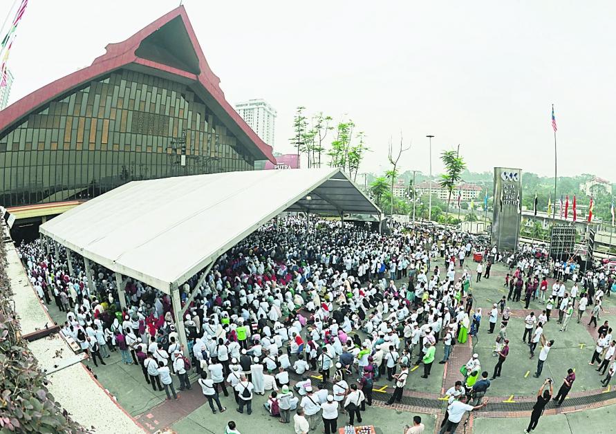 吉隆坡世界贸易中心外人潮拥挤,即便期间下雨,党员也坚持留守到活动结束。