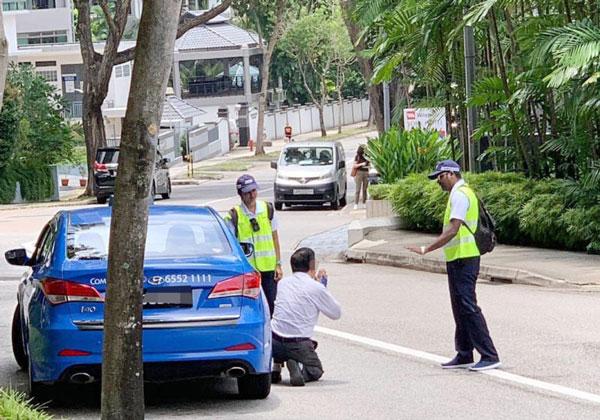 德士司機因在車上抽菸被開罰,當場跪地向執法人員求情。(取自面子書)