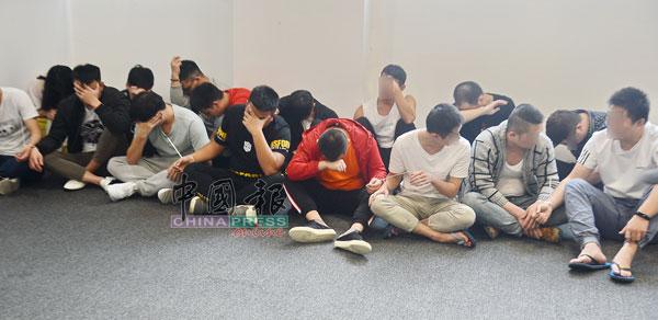 27名中国籍男女在一旁等候警方盘查。