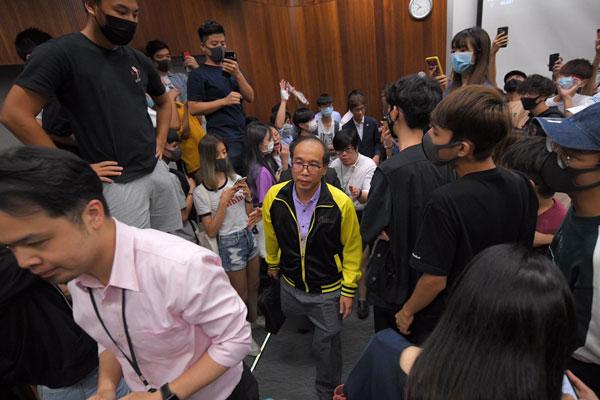 """陈伟强被学生包围,受困于课室内,课室内的荧幕投影写着""""平反六四""""字句。"""