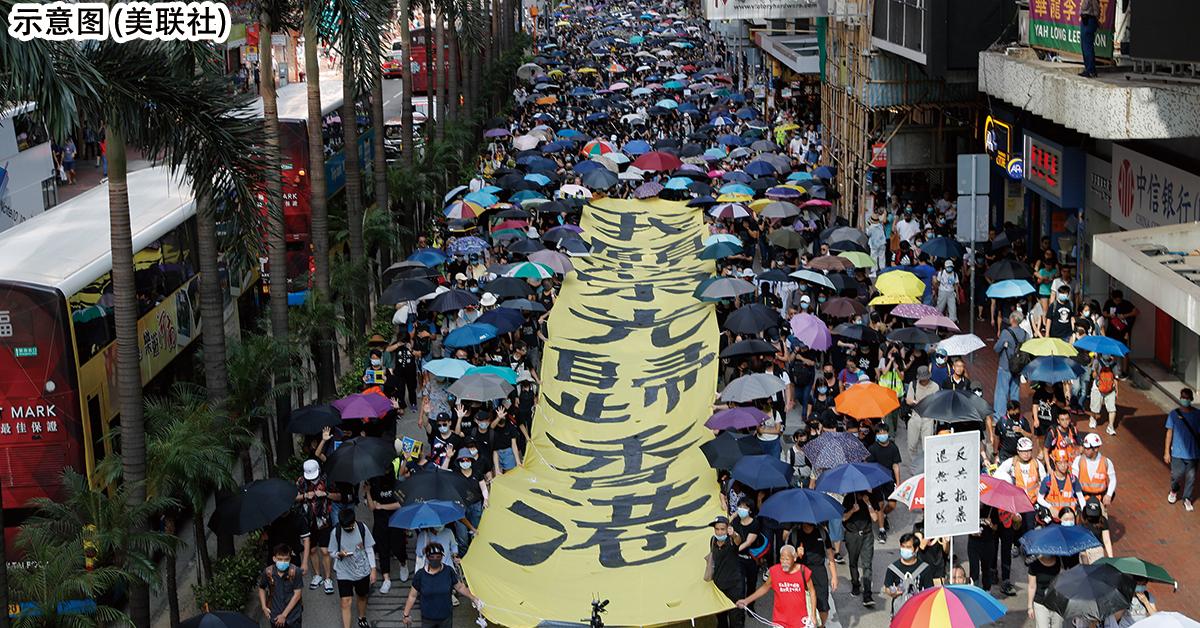 """香港反送中示威者手持雨伞并拉着""""愿荣光归香港"""" 布条上街游行。(档案照) (美联社)"""
