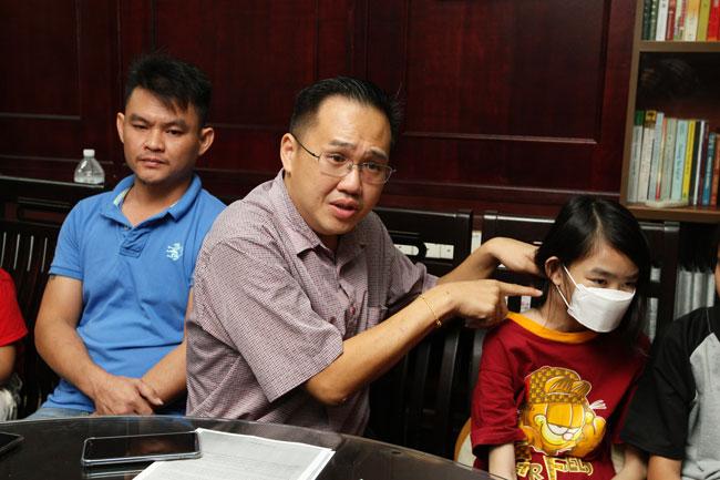 李杰文(中)指着晓燕的颈部说,她爸爸看到女儿右边的颈项肿起来,求医后进而发现已患上第3期淋巴癌。左为王文初。