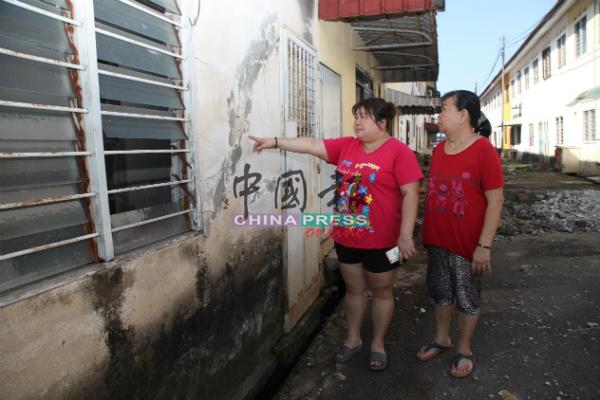 谢秀音(左起)与陈丽华看着龟裂的墙壁,不胜唏嘘。