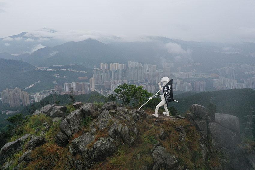"""矗立在香港狮子山的港版""""民主女神像"""",高4公尺,手执旗、雨伞、穿着防护装备及戴上头盔、脚踏催泪烟。(欧新社)"""