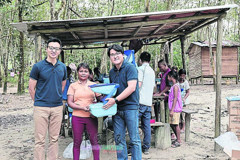 郑泰升陪同Coway马来西亚董事经理崔起龙(右),赠送简易家用版的过滤设备给原住民家庭。