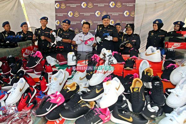 莫哈末兹克里阿占(左5)与贸消局执法员动用剪刀,剪破在检举行动起获的国际名牌仿冒运动鞋。