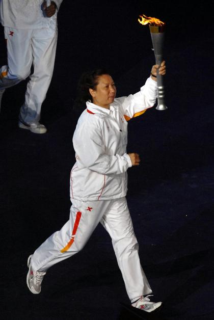 2007年10月25日,韩爱萍在武汉举行的第6届全国城市运动会开幕式上传递火炬。(新华社档案)