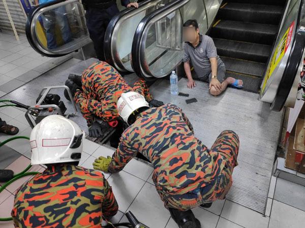 消拯员拆除手扶梯的铝板,以把伤者受夹在手扶梯内的右腿移出。