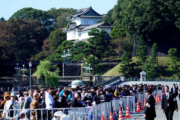 日本民众周日聚集在皇宫前的院子,希望能观看日皇夫妇车队游行的盛况。(美联社)