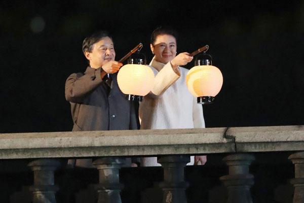 """日皇德仁(左)和皇后雅子周六出席天皇即位的""""国民庆典"""",两人手持灯笼。(法新社)"""