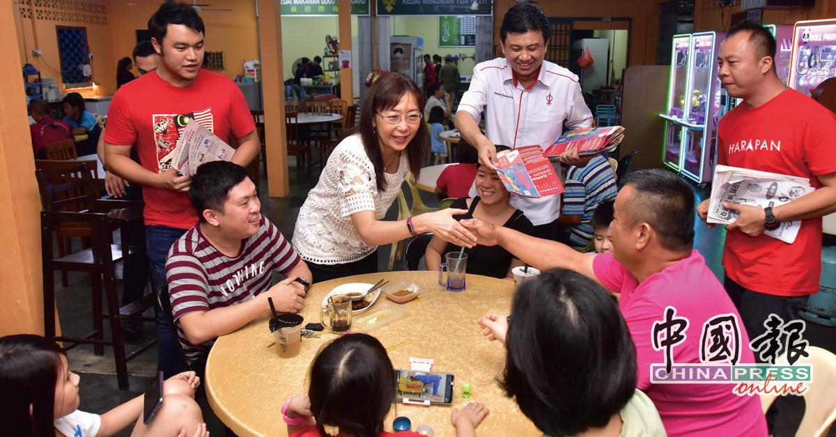 郭素沁(站者左2)与民众握手交流。