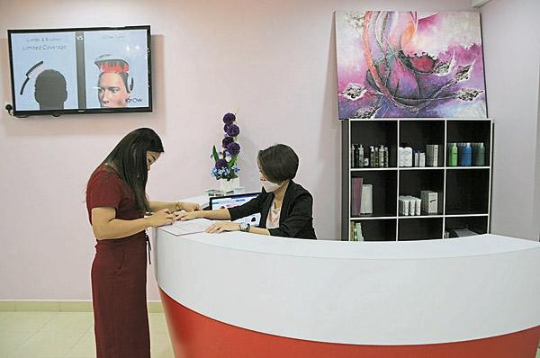 步骤1:顾客在 Mediskin Hair Centre 柜台处,咨询头发护理和养发讯息。