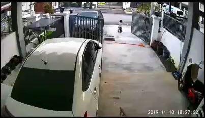 孩童骑着儿童脚踏车冲向马路,一旁洗车的男子对此毫无察觉。