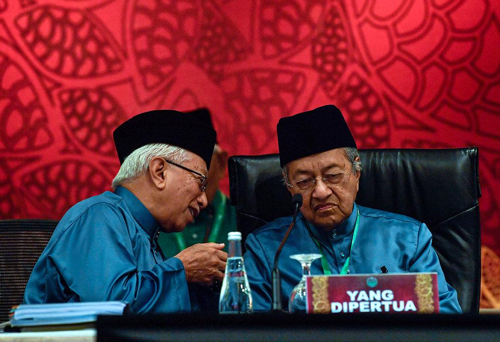 马哈迪(右)在大会上与马来西亚穆斯林福利组织总秘书丹斯里莫哈末尤索夫交流。