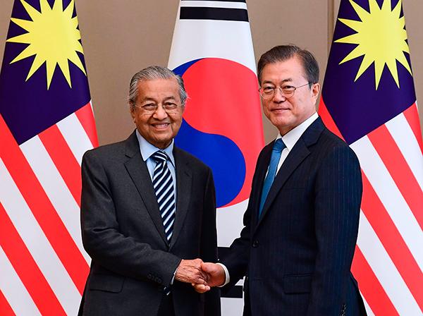 马哈迪(左)与文在寅在会谈前互相握手。