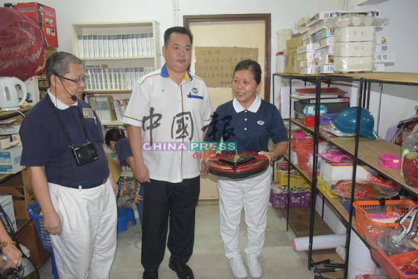罗绣甄(右起)向赖水和讲解慈济如何处理可再使用的物品。左是张佛生。