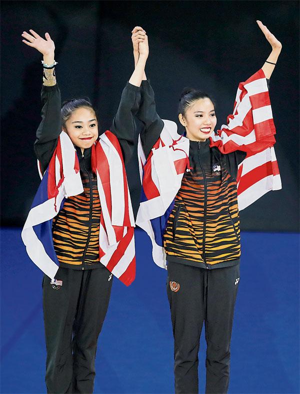 依查(左)与郭雪嫣庆祝夺得金牌。两人在带操共享金牌。(欧新社)