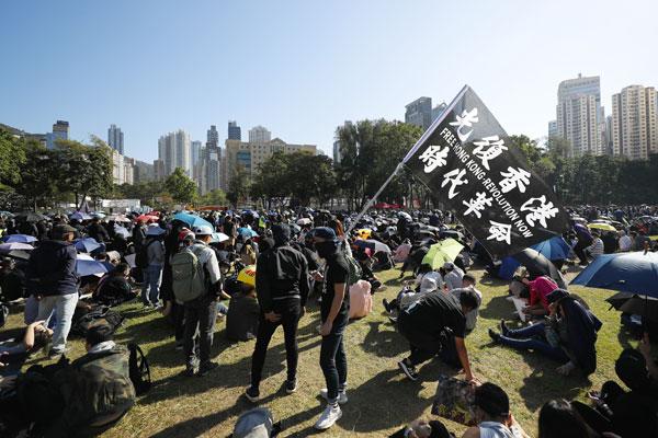 """示威者挥动黑色旗帜,旗上写着""""光复香港,时代革命""""。(美联社)"""