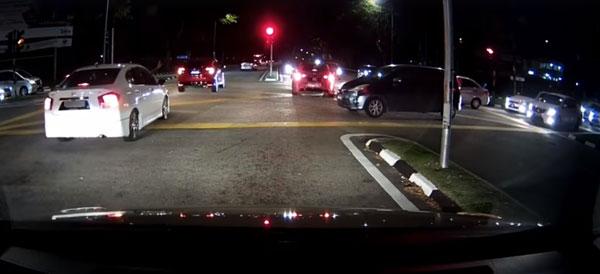 红色轿车拦着右方正在绿灯行的轿车,让后方的车队闯红灯。