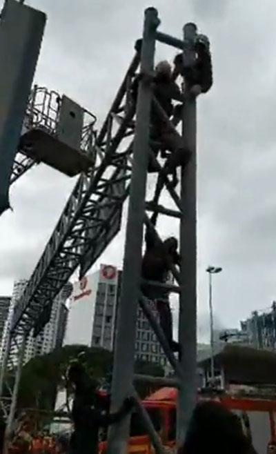 消拯员和警员爬上铁架把企图自杀的外劳制伏。