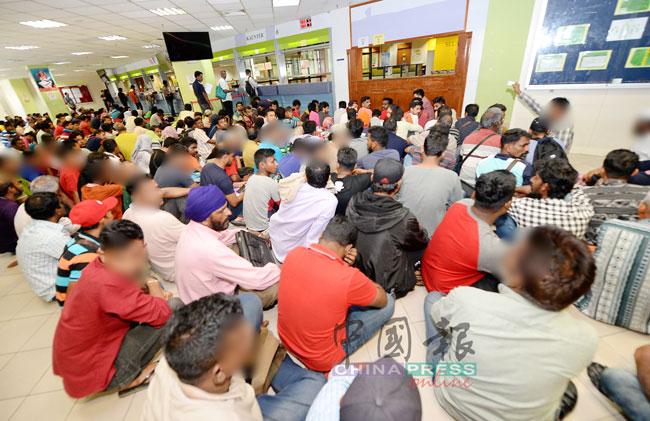 大批外劳赶在非法外劳自愿遣送计划迈入尾声时,前往移民局提出申请,他们在移民局官员指示下,有秩序地坐在地面上,等候办理手续。(档案照)
