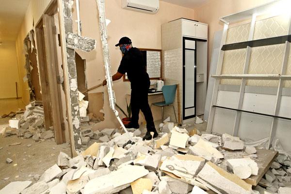 市政厅执法人员将房间内的床架移走后,再将房间隔拆除。