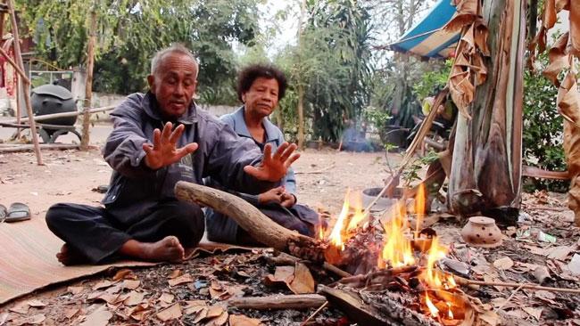 一对老夫妇在火堆旁取暖。