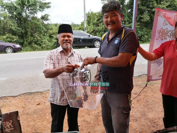 路经的友族同胞,购买水果支持拉曼。右为侯西业。