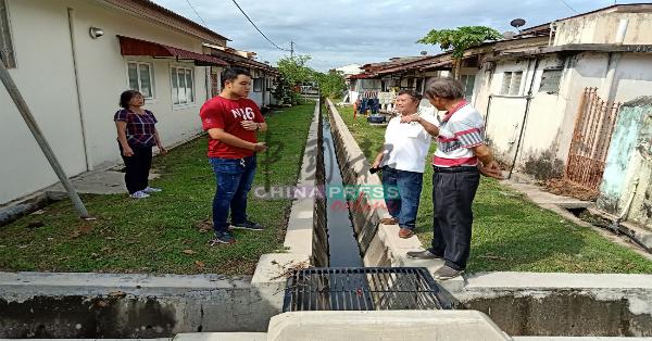 郭子毅(左)视察合作花园后巷的排水沟。