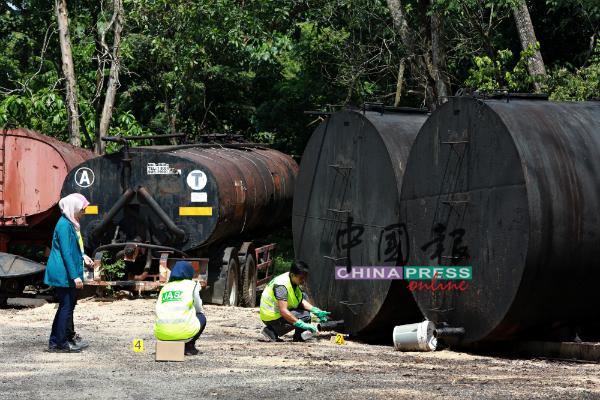 环境局官员从大油桶抽取样本。