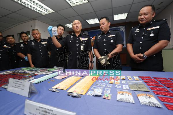 莫哈末卡马鲁丁(右3起)在李庆泉及多名警官陪同下,展示柔州肃毒组所起获的各类毒品和充公的财物。