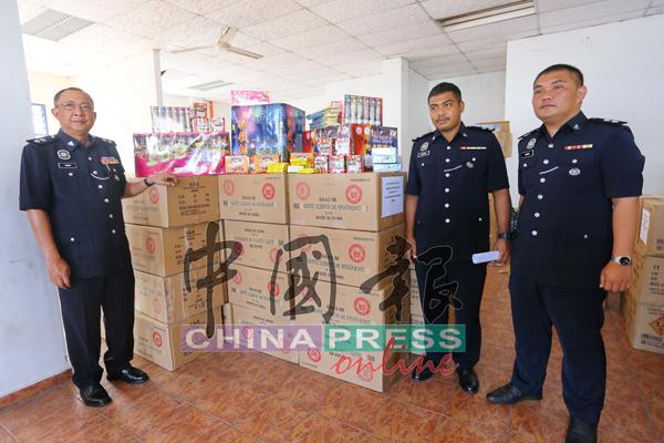 阿末峇迪(左)与查案官,展示收放在警局货仓内的大批烟花炮竹。