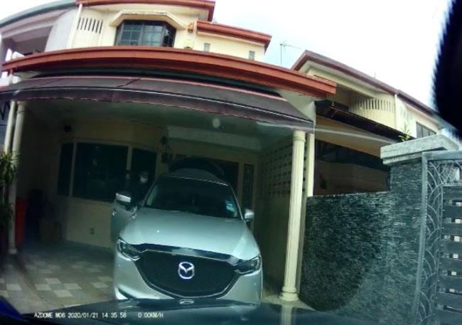 戴着口罩的匪徒发现屋主驾车回家后,马上打开车门进入车内准备逃走。