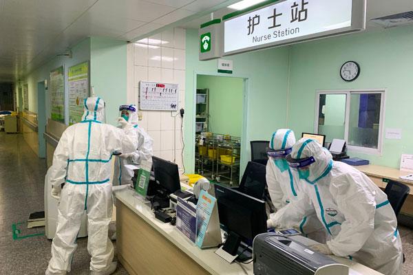 武汉大学中南医院医护人员周三身穿防毒衣。(法新社)
