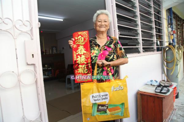 一位东街纳组屋居民喜获由州政府派送的春联与福袋。