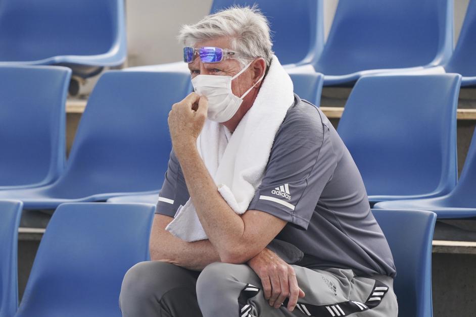 一名现场观众配口罩观看球员们练习。(美联社)