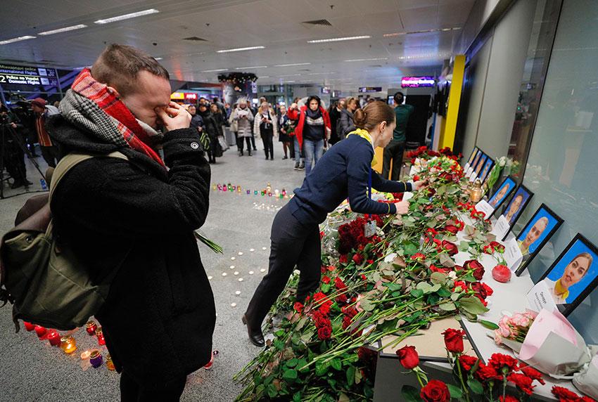 乌克兰鲍里斯波尔国际机场,周三为失事客机机组人员举办追悼会。一名空服员的伴侣站在遗照前,悲从中来,掩面哭泣。(欧新社)
