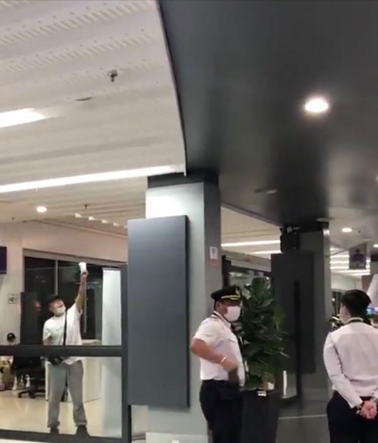 男子爬玻璃墙失败后,试图要把一份文件交给机场的保安员。