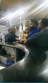 PAPAGOMO在柜台处被朋友用身体保护,避免他与对方发生进一步冲突。