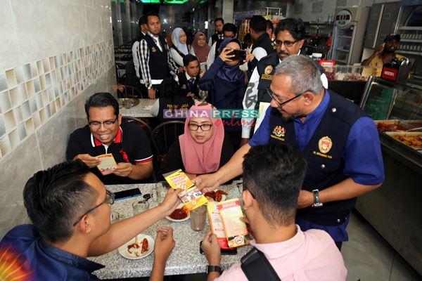 莫哈末法益医生(右)到嘛嘛餐馆展开突击检查行动,顺道派发禁烟令小册子予市民。