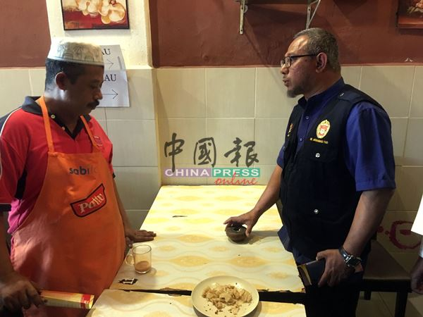 莫哈末法益(右)询问餐馆业者既然餐馆禁烟,为何餐桌上出现烟灰缸?