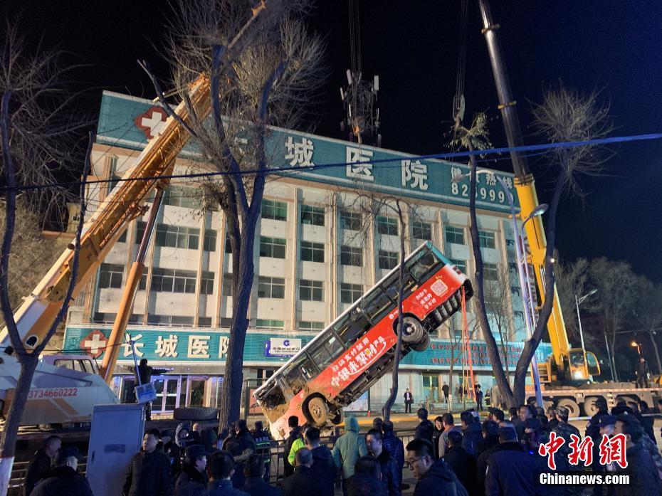 西宁周一发生地陷,巴士跌入坑,救灾人员吊起巴士。(中新网)